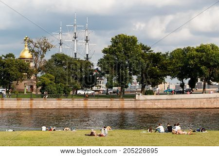 SAINT PETERSBURG, RUSSIA - AUGUST 18, 2017: People resting on the banks of the Neva river at the Peter and Paul fortress on background of Church Holy Trinity chapel and the masts of the Frigate.