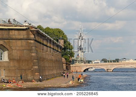 SAINT PETERSBURG, RUSSIA: August 18, 2017: People sunbathing at granite boundary wall of Peter and Paul fortress    in Saint Petersburg on background Trinity bridge and frigate masts. View from Commandant's Jetty.