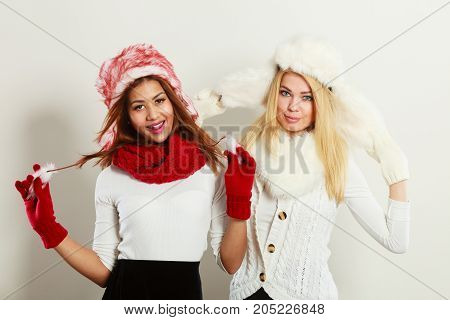 Fashion winter outfit concept. Two happy smiling girls blonde and mulatto in warm red white clothing portrait. Attractive women wearing fur caps scarfs gloves.