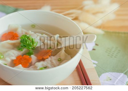 Close up minced pork wonton soup in white bowl on wood cutting board on wood table. Homemade delicious wonton in clear soup for breakfast or lunch or dinner. Wonton soup is popular Chinese food. Wonton soup ready to served on wood table.