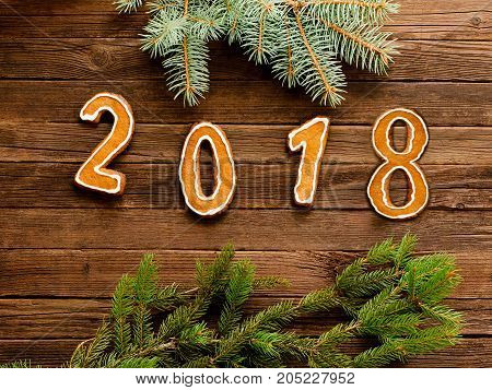 New Year's Concept. The Figure In 2018 Of Gingerbread On A Wooden Background, Fur-tree Branch