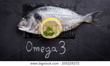 Raw dorada fish laying on black slate and written word omega 3 by white chalk.