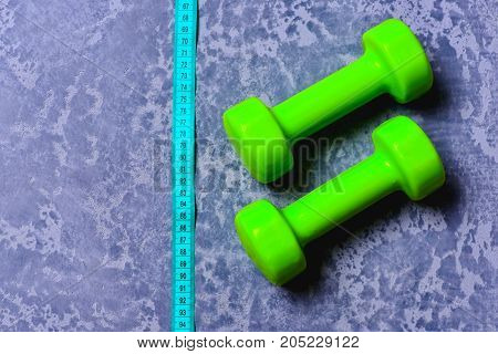 Dumbbells In Green Color And Measuring Tape On Grey Texture