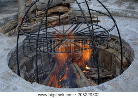 in the pit a construction of metal rods for smoke. metal structure for cooking on fire