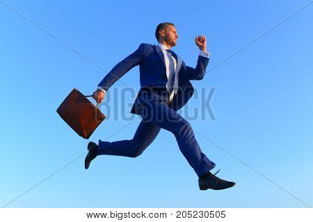 Businessman makes big step up on career ladder. Business and success concept. Project manager with strict face expression. Man in blue formal suit holds brown case and jumps up on blue sky background