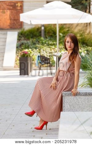 Beauty feminine details outfit ideas concept. Woman in long pink dress sitting on city street bench relaxing.