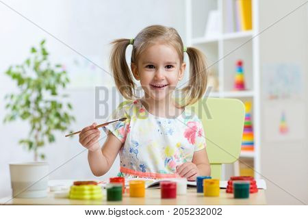 Cute child little girl painting in kindergarten