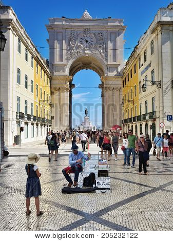 Lisbon Portugal - June 11 2017: The little girl listens to the street musician playing music nearby square Praca do Comercio for the tourists and citizens