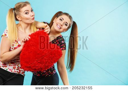 Happy two teenager women holding heart shaped pillow. Valentines day gift ideas teenage love concept.