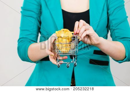 Buying gluten food products concept. Woman hand holding shopping cart trolley with small piece of bread or sweet bun