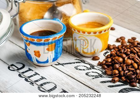 two different hand-painted Vietri ceramic coffee cups and coffee beans and cane sugar on white wooden tray