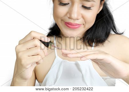 Picture of a beautiful woman using nail polish on her fingernails isolated on white background