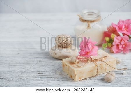 Natural handmade soap aromatic oil and flowers on white wooden background. Spa concept.