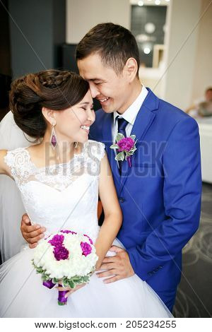 Charming couple bride and groom in the lobby laughing and genuinely smiling positive portrait. Sincere feelings. Wedding bouquet in hands, all in one color scheme.