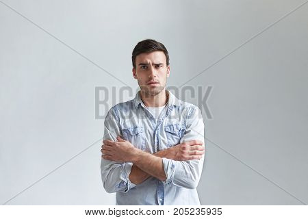 Angry suspicious young Caucasian man standing in closed posture as sign of protection holding arms crossed on his chest. Grumpy and dissatisfied guy posing in studio displeased with something