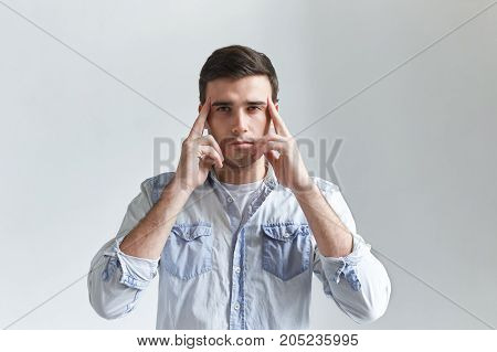 Headshot of concentrated young man thinking about something holding fingers on his temple trying to recollect something. Thoughts ideas brainstorming bad memory concentration or headache concept