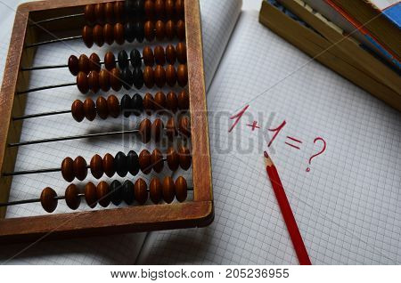 wooden abacus , a notebook in a cage with the first example of arithmetic for students