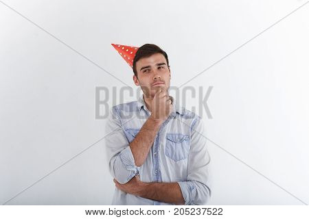Body language and non verbal communication. Young unshaven brunette male wearing blue jeans shirt and red holiday hat looking sideways and touching his chin having suspicious facial expression