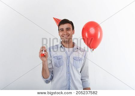Waist up shot of good looking positive young man with stubble holding red helium balloon and whistle smiling broadly having fun on party. People joy entertainment and celebration concept