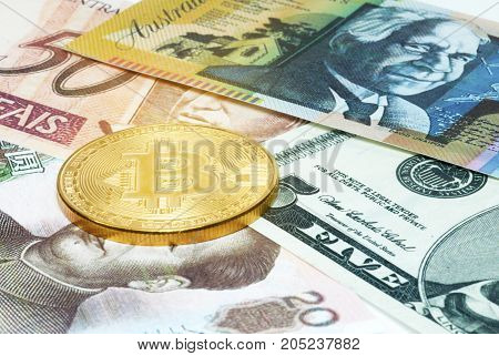 The Bitcoin Gold Coin is placed on a banknote denominated in dollars.