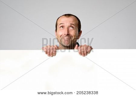 Hispanic man holds the blank sign and looks up in a studio white background. Copyspace for text or ad