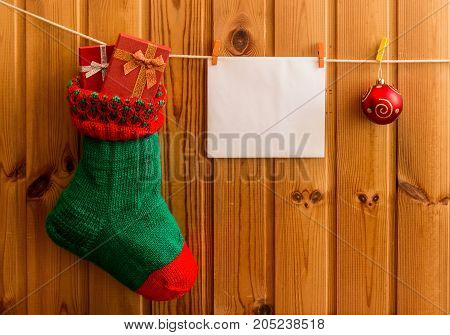 Christmas stocking and greeting card on wooden wall