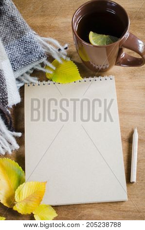 A cup of hot tea with lemon and empty notebook for sketch plaid on a rustic table yellow leaves. Cozy autumnal mood warm autumn.
