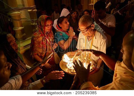People getting blessings from the holy fire during the morning darshan inside the Sri Krishna Balaram Mandir temple ISKCON temple of Vrindavan. Uttar Pradesh India. - July 2017.