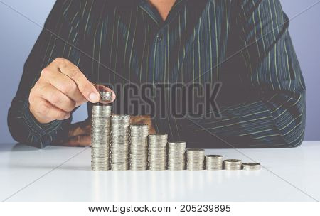 Saving money concept and hand of businessman putting money coin stack growing for business. Financial and saving concept.