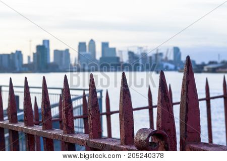 Rusty Gate With Canary Wharf In London In The Background For Concept Use