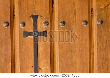Background of a brown door with a cross