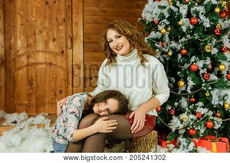 Mom with daughter next to Christmas tree