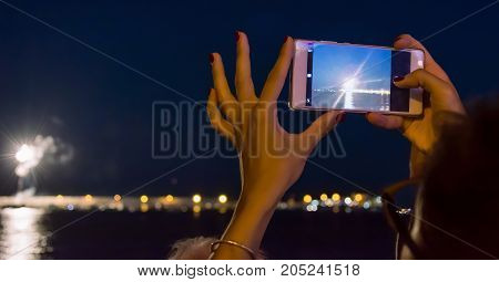 woman holding a mobile smart phone to take photo of firework