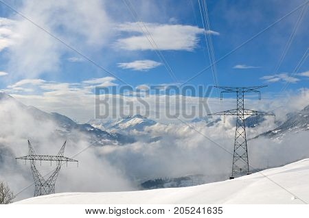 electric high voltage towers in snowy alpine mountain
