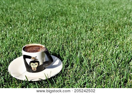 Turkish coffee. coffee grounds on the bottom of the mug. a cup on the grass. green meadow and white tableware. fortune telling, monkey cup, monkey background, funny and cute cup, green background
