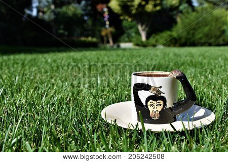 coffee time. coffee grounds on the bottom of the mug. a cup on the grass. green meadow and white tableware. fortune telling, monkey cup, monkey background, funny and cute cup, green background