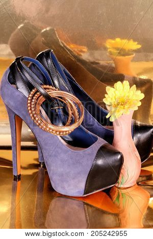 Sexy blue suede high heel shoes, bracelets, vase and yellow flower on gold foil background.