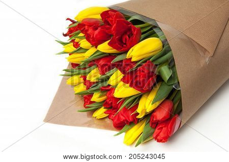 yellow and red tulips in a paper bouquet closeup. Valentine's Day