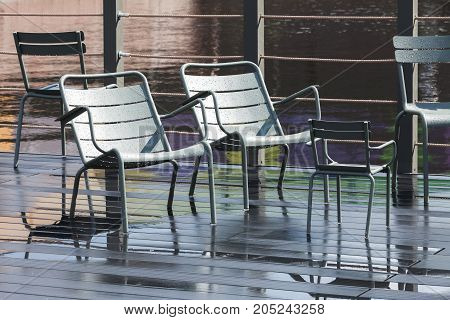 Empty Outdoor Gray Metal Chairs Stand On Pier