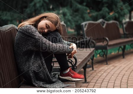 Young female with blond hair sitting on the bench in the park. Positive teenage girl dreaming on the bench. Cold autumn weather. Art concept