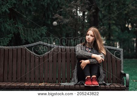 One teenage girl with blond hair in knitted cardigan and black denim jeans sitting on wooden bench in the park. Autumn vibes