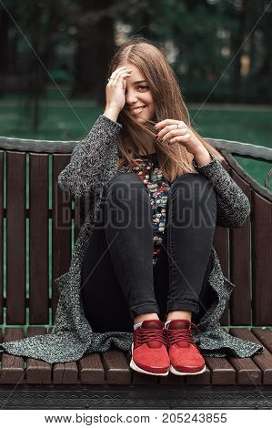 Happy and cheerful teenage girl sitting on wooden bench in the park. Autumn mood. Young model