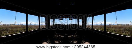 View from inside of an abandoned and rusty old Soviet Russian bus in the middle of reeds and agriculture fields with snow-capped scenic Ararat mountain and clear blue sky on the background in rural Southern Armenia in Ararat province on 4 April 2017.