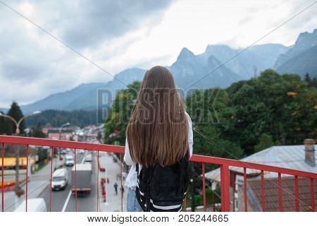 Young girl traveler looking at the mountains from the bridge. Part 2.
