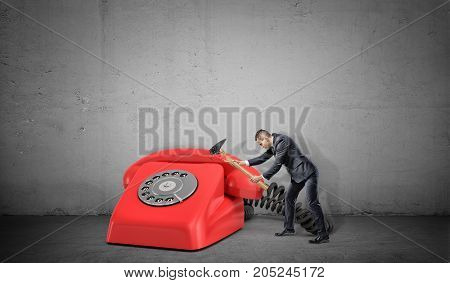 A small businessman fails to destroy a large red retro phone with a broken hammer. Too many calls. Need for optimization. Time wasters.