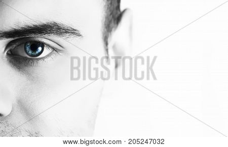Man looks at the camera on a white background half face with blue eye