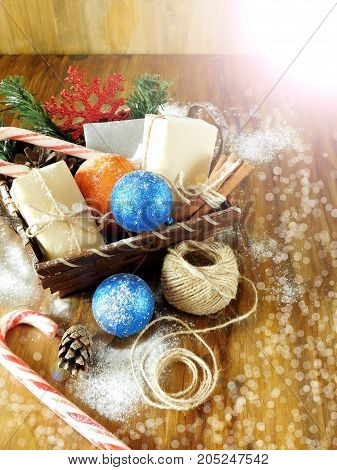 Basket full of Christmas attributes and present boxes on a wooden background. Photo with special editing