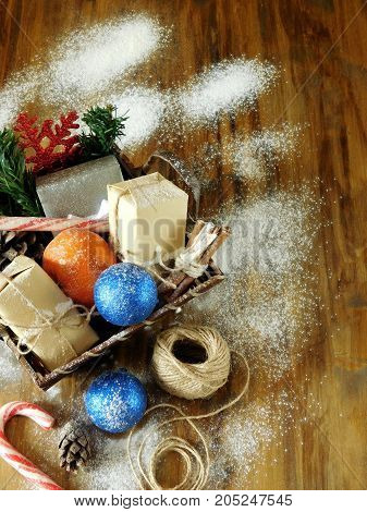 Basket full of Christmas attributes and present boxes on a wooden background. Christmas composition