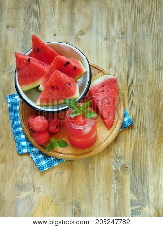 Watermelon segments and a refreshing drink with ice and decorated with mint on a wooden table. View from above