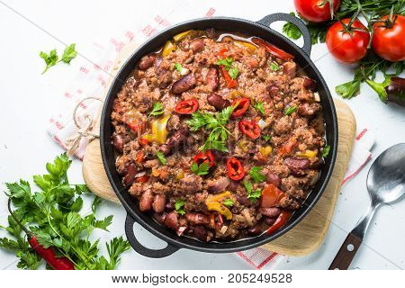 Chili con carne in a cast iron pan on white. Traditional mexican food. Top view.